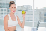 Smiling sporty blonde holding green apple