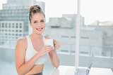 Smiling athletic blonde holding coffee