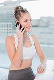 Cheerful athletic blonde having a call