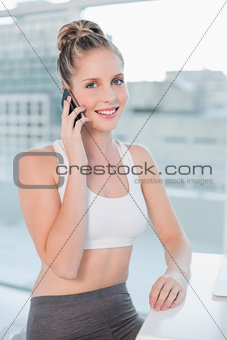 Smiling athletic blonde having a call