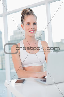 Smiling athletic blonde typing on laptop
