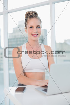Smiling athletic blonde using laptop