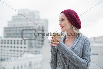 Thoughtful casual blonde holding coffee outdoors