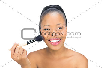Attractive woman applying powder to face with brush