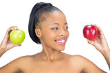 Attractive woman holding red and green apple looking at the red one