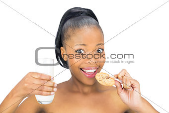 Attractive woman drinking milk and holding biscuit