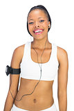 Smiling woman in sportswear listening to music