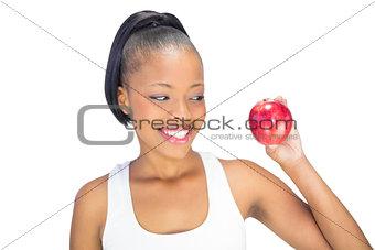 Fit woman wearing sportswear looking at red apple