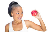 Happy woman in sportswear looking at red apple