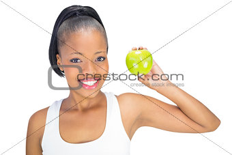 Attractive woman in sportswear showing green apple