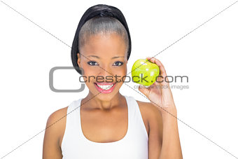 Attractive woman in sportswear holding green apple