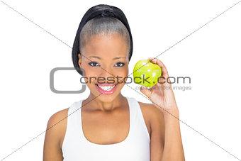 Attractive woman in sportswear holding green apple