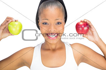Fit smiling woman holding red and green apple while looking at camera