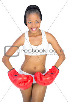 Fit woman with red boxing gloves posing
