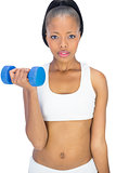 Serious woman in sportswear working out with dumbbell