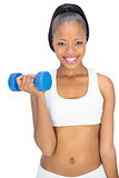 Happy fit woman in sportswear working out with dumbbell