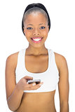 Smiling woman in sportswear holding phone while looking at camera