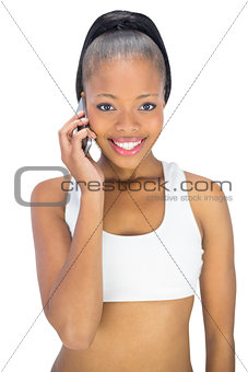 Fit woman in sportswear talking on phone while looking at camera