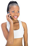 Smiling woman in sportswear talking on phone
