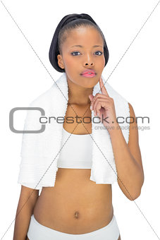 Thoughtful woman in sportswear with towel around her neck