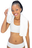 Smiling woman in sportswear using towel