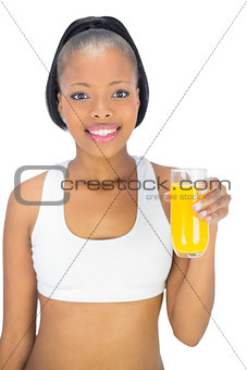 Fit smiling woman holding glass of orange juice
