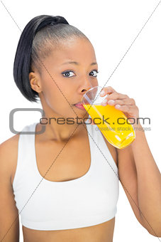 Fit woman drinking glass of orange juice while looking at camera