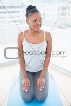 Attractive woman sitting on exercise mat