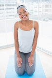 Laughing woman sitting on exercise mat