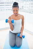 Fit woman in sportswear sitting on exercise mat and working out wiht dumbbell