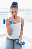 Woman sitting on exercise mat working out with dumbbell