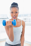 Fit woman working out wit h dumbbell while looking at camera