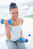 Exerted woman working out with dumbbell
