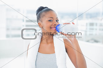 Fit woman with towel around her neck drinking water while looking at camera