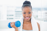 Smiling woman with towel around her neck working out with dumbbell