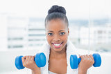 Fit woman with towel around her neck working out with dumbbell