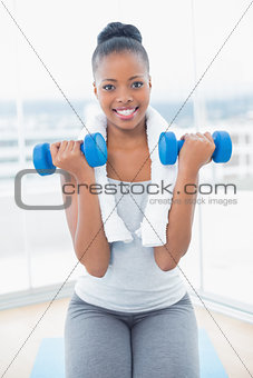 Fit smiling woman with towel around her neck working out with dumbbell