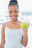Smiling slender woman in sportswear holding green apple