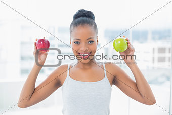 Attractive woman holding green and red apples