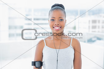 Fit woman in sportswear listening to music
