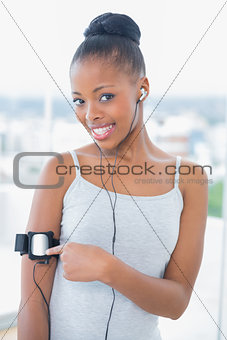 Fit woman in sportswear using her music player while looking at camera