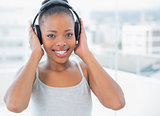 Smiling woman listening to music with headphones