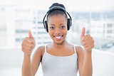 Smiling woman listening to music with headphones and giving thumbs up