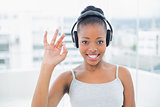 Smiling woman listening to music with headphones and shwoing okay sign