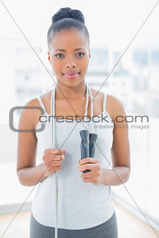 Fit woman in sportswear holding jump rope