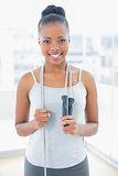 Fit happy woman in sportswear holding jump rope