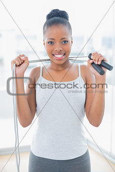Fit woman in sportswear holding jump rope around her neck