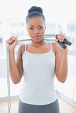 Serious woman in sportswear holding jump rope around her neck