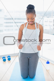 Fit woman in sportswear holding measuring tape around her neck