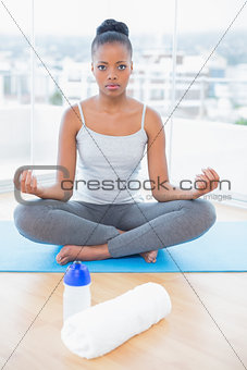Serious woman practicing yoga while looing at camera